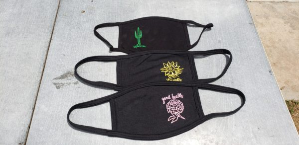 """three handmade fair trade black face mask with screen printed designs on the sides of the masks. The three designs from front to back are of a soft pink chrysanthemum with the text, """"good health"""" above it in cursive, a yellow sunflower motif with the word, """"Strength"""" below it, and a green two-limbed saguaro cactus with the word, """"endurance"""" below it."""