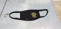 "handmade fair trade black face mask with a yellow, screen printed design on the right-hand side of the mask of a sunflower with the word, ""Strength"" below it in cursive."