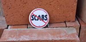 """White Button with Red """"No-Symbol"""" across degraded text reading, """"SCABS"""" resting on stacked bricks"""